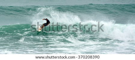 WARKWORTH, NZL - JAN 26 2016:Man surfing in Tawharanui Regional Park.It's one of the best surfing location in the North Island of New Zealand due to perfect pacific ocean wave surf conditions.