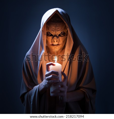 Warlock with candle in darkness. - stock photo