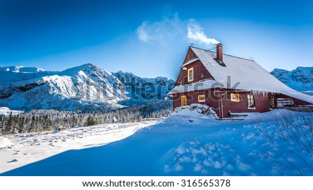 Warm accommodation in a mountain cottage in winter - stock photo