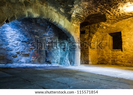 Warm and cold light in stone chamber - stock photo