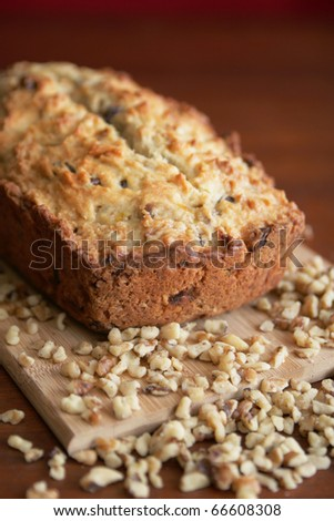 Warm and fresh nuts bread with nuts on a wood cutting board - stock photo