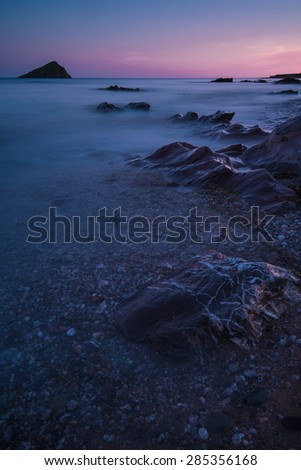 Warm and tranquil seascape at rocky beach at twilight, with water motion blur - stock photo