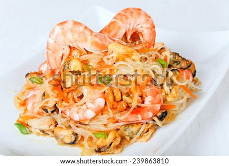 Warm asian salad with cellophane noodles, shrimp and mussels closeup. - stock photo