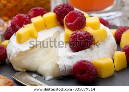 Warm baked Brie cheese with fresh mango and raspberries - great snack for cocktail party. Couple of cocktails in background.