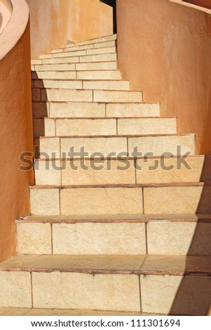 Warm beige stones wind upwards towards the top of a staircase in Belize City, central America - stock photo