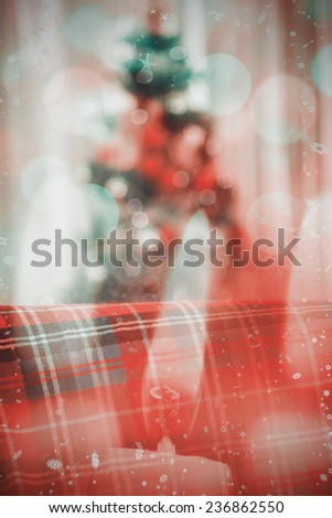 Warm blanket on the couch at christmas against candle burning against festive background - stock photo