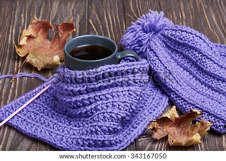 Warm cap, scarf and hot drink in cold weather
