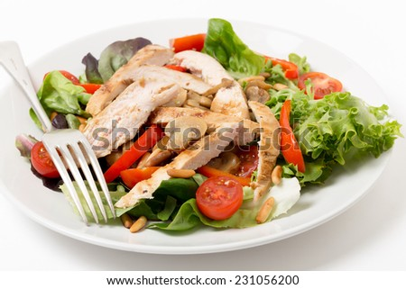 Warm chicken and mushroom salad, with  lettuce, cherry tomatoes, pine-nuts and strips of pepper - stock photo