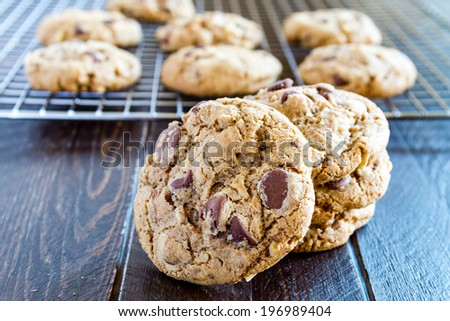 Warm chocolate chip cookies sitting on cooling with stack of cookies in front