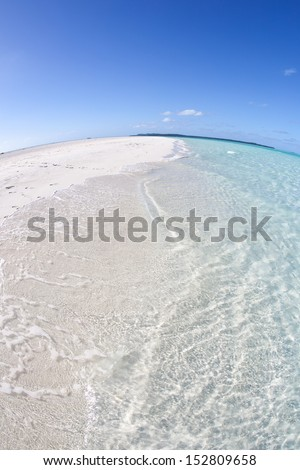Warm, clear water washes up on an idyllic white sand beach in French Polynesia. - stock photo