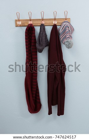 Warm clothings hanging on hook against wall
