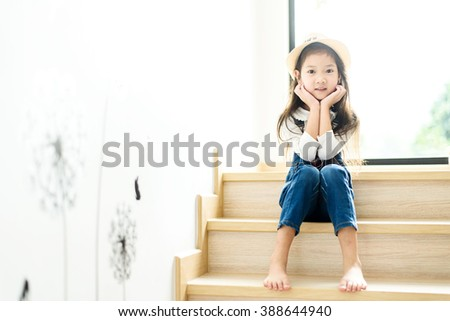 Warm color tone.Portrait young Thai girl sit on the step at home beside the glass window - stock photo
