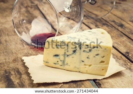 Warm color toned image of cheese and wine background. Blue cheese with overturned wineglass. - stock photo