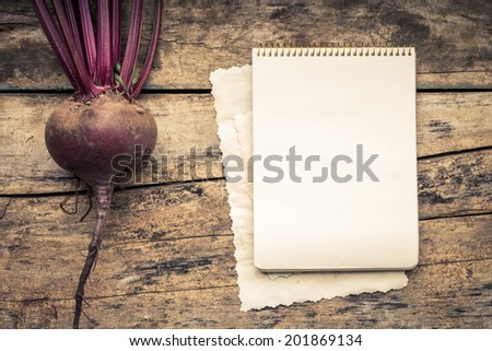 Warm color toned series of Vegetables with recipe book on wooden table. Old wood background. Menu background. Red beet. - stock photo