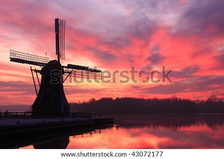 Warm colors of a cold winter sunset at Dutch windmill. - stock photo