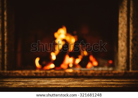 Warm cozy fireplace decorated for Christmas with real wood burning in it. Cozy Christmas concept. Christmas background with space for your text. - stock photo