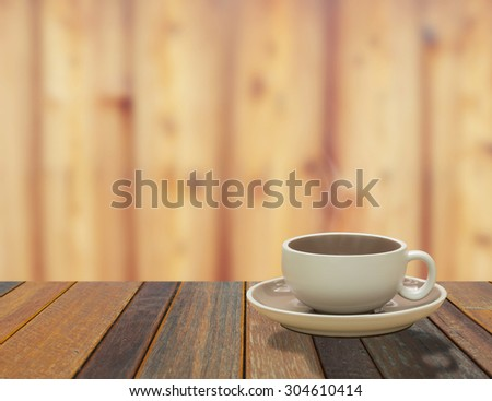 warm cup of coffee on brown wood background