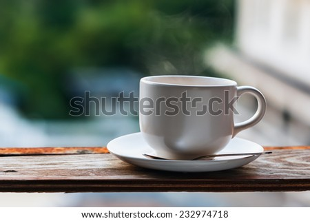warm cup of coffee on green nature background