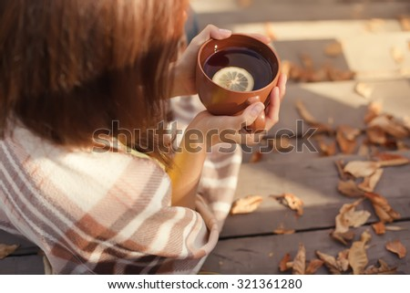 warm cup of hot coffee warming in the hands of a girl, autumn outdoors - stock photo