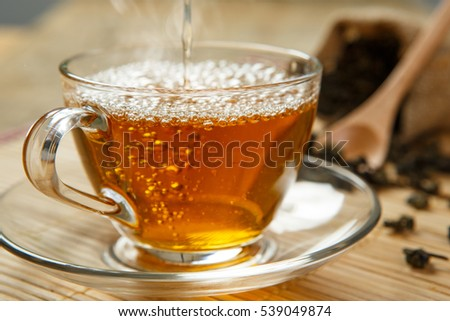 Warm cup of tea and leaves tea on wooden placemat