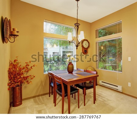 Warm dining room with carpet windows, table and chairs.