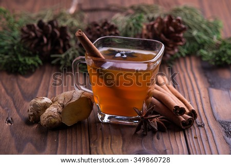 Warm drink for winter: tea, cinnamon, star anise, and ginger - stock photo