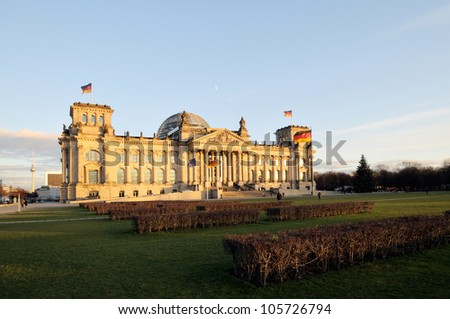 Warm evening sunlight illuminating the mighty Reichstag parliament with clear blue sky and flags flying. - stock photo