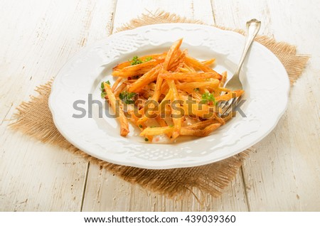 warm french fries with red pepper, salt and parsley served on white plate - stock photo