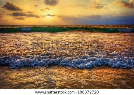 Warm gold sunrise over crashing ocean waves - stock photo