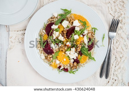 Warm Healthy Salad from quinoa, brown rice, cooked beetroot, oranges, wild rocket salad, goats cheese or feta and handfuls of walnut pieces