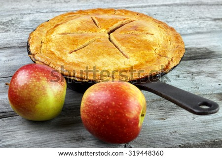 Warm homemade apple pie on skillet with two apples on gray wooden surface - stock photo