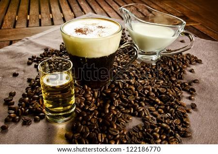 Warm Irish Coffee with coffee beans, whiskey and cream - stock photo