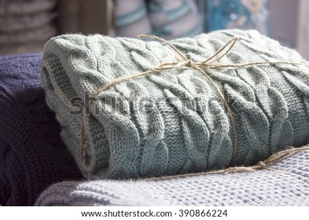 Warm knitted blankets folded stack. Plaid mint color over blue homemade quilts, hand-knitted. The cosiness and comfort in the cold winter - stock photo