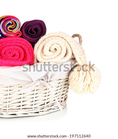 Warm knitted scarves in basket isolated on white - stock photo