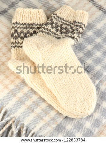 Warm knitted socks on plaid close-up - stock photo