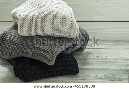 warm knitted sweater, three pieces, black,grey and white on a wooden white background, closeup - stock photo