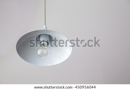 Warm lighting coming out from beautiful lamps on ceiling. Electric lamp in dark in a cafe.