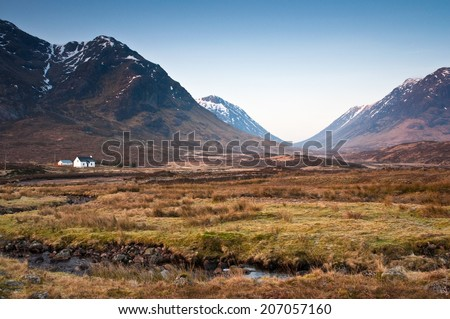 Warm magenta hues from the first rays of morning sunlight illuminating pretty white cottage and dramatic mountains of Glen Coe, Scottish Highlands. - stock photo