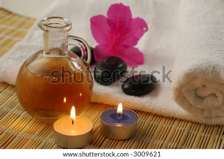 Warm massage oil, candles and stones and towel