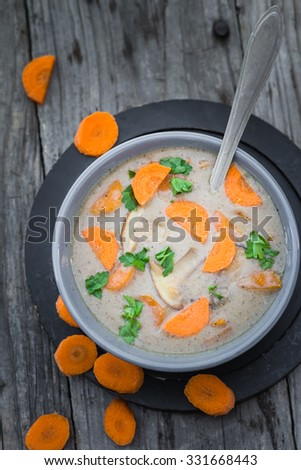 Warm meal: mushroom soup with carrots and parsley on a wooden table