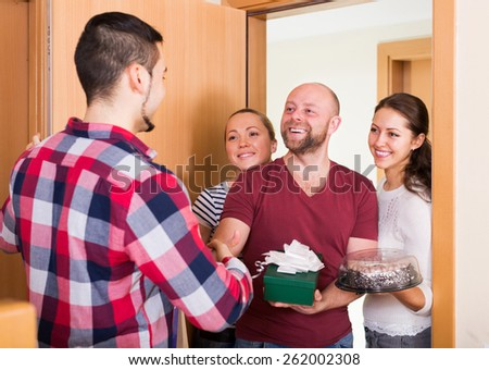 Warm meeting of casual friends holding gifts and sweets - stock photo