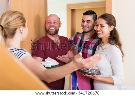 Warm meeting of smiling friends holding gifts and sweets