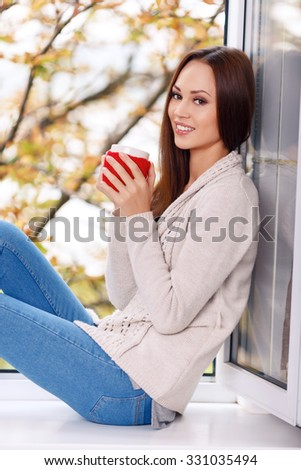 Warm moment. Waist up selective focus of charming young girl who is sitting on the windowsill and enjoying her drink with a grin. - stock photo