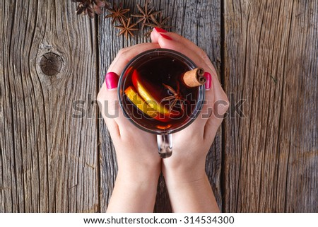 Warm mulled wine in female hands, spices on weathered wooden table. Top view - stock photo