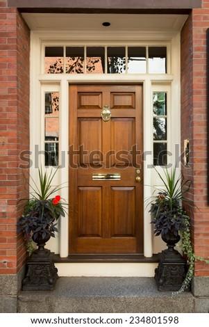 Warm Natural Wooden Door with Surrounding White Door Frame and Windows - stock photo