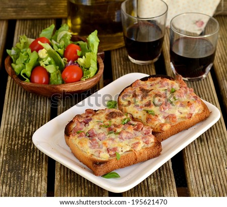 Warm open faced sandwiches with ham, cheese and sour cream served with green salad and red wine. Selective focus - stock photo