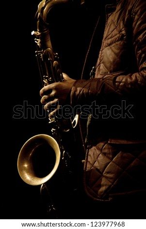 Warm photo of the male saxophonist playing in sax - stock photo