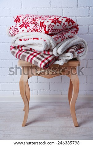 Warm plaids on small wooden table and white brick wall background - stock photo