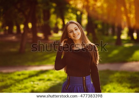 Warm rays of evening sun beautifies younf blonde standing on the lawn