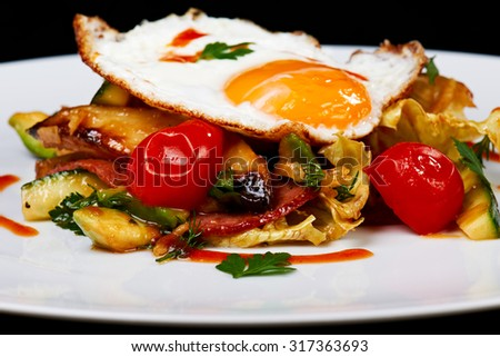 Warm salad of roasted zucchini, potatoes, tomatoes, cabbage and bacon with a fried egg on a top.